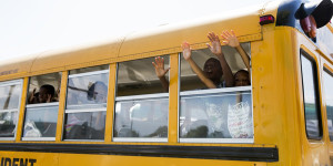"School bus full of children gesture and chant ""hands up, don't shoot"" as they drive past the scene of where, according to local media, police shot dead a 23-year-old man wielding a knife in the St Louis area"