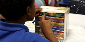 Boy looks through stack of books