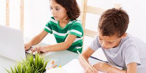 two kids sitting at desk doing homework