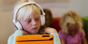 Young girl with headphones playing a game on an ipad