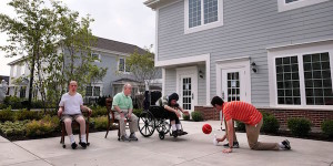 adults with disabilities in driveway playing basketball