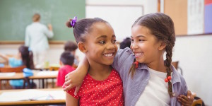 two girls in a classroom with their arms around one another