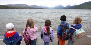 young students standing looking over a lake