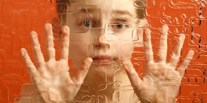 Student with autism looking through glass