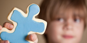 Autistic child holding blue puzzle piece