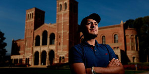 Latino student in front of college building