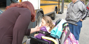 student with wheelchair going on bus