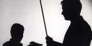 silhouette of a man hitting a child with a stick