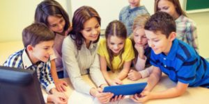 teacher and group of children crowding around a tablet