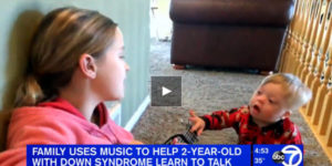 toddler with Down Syndrome singing with sister playing guitar