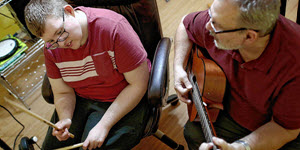 teen with PWS syndrome drumming with father playing the guitar