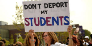 """teaching holding up sign """"don't deport my students"""""""