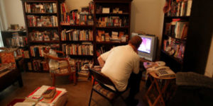 adult staring at computer surrounded by books