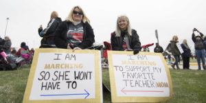 moms holding signs for teacher protest