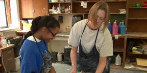 blind female art teacher helping young blind female student