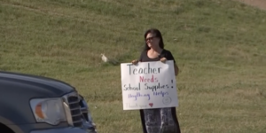 teacher holding up a sign asking for money