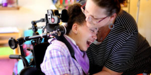 girl in wheelchair crying with caregiver