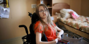 girl with cerebral palsy in wheelchair looking unhappy