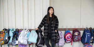 young female asian teacher with row of backpacks