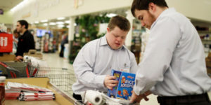 young man helping older man to bag groceries