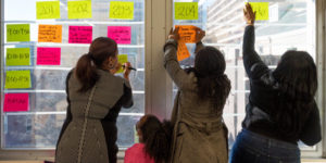 teachers posting sticky notes on window