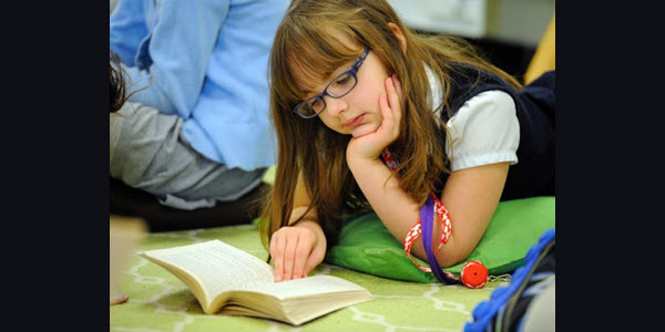 young girl with glasses reading